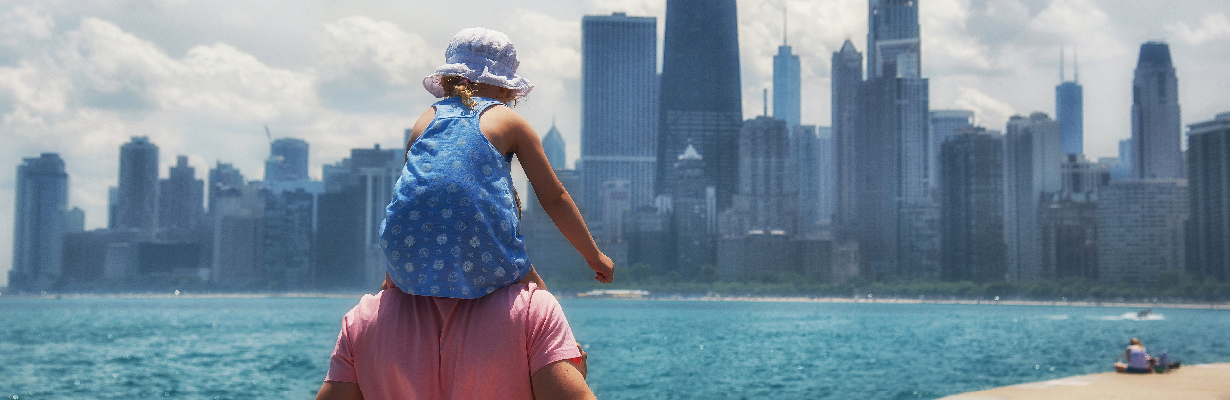 Little girl sits on her father's shoulders with Lake Michigan and the Chicago skyline in front of them.